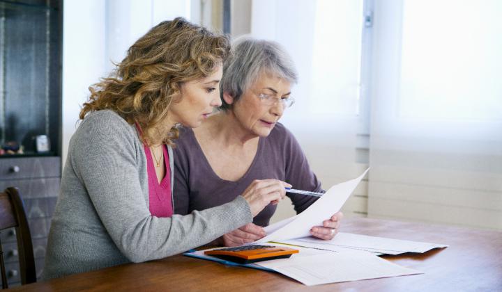 Twee vrouwen lezen een brief met pen in de hand.